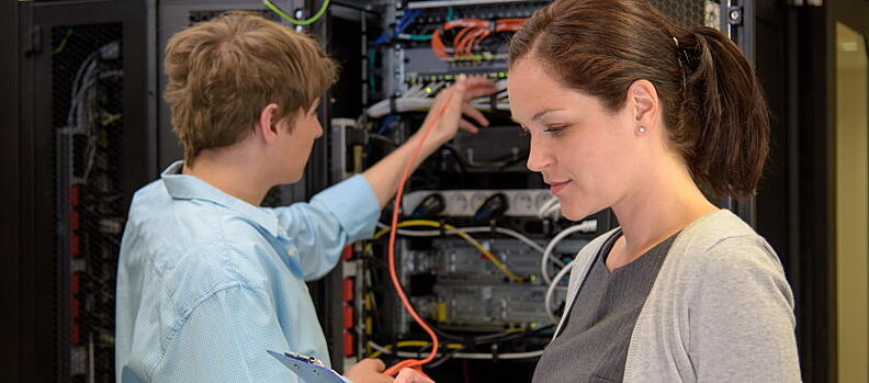 Two engineers working on IT infrastructure in a data centre