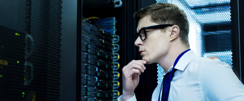 Man looking at server colocation rack in a data centre
