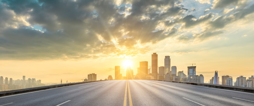 Sunrise over a city skyline and a highway