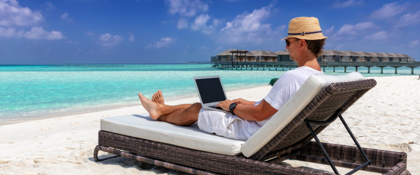 Business owner working on a beach with a laptop