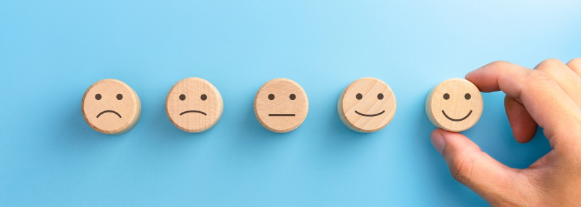 Customer survey wooden smiley faces on a blue background